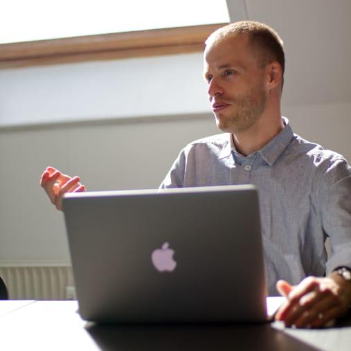 mand med macbook holder møde