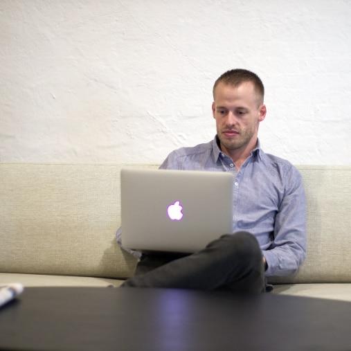 mand-sidder med-macbook